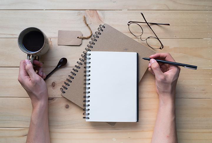 caderno, café óculos mãos