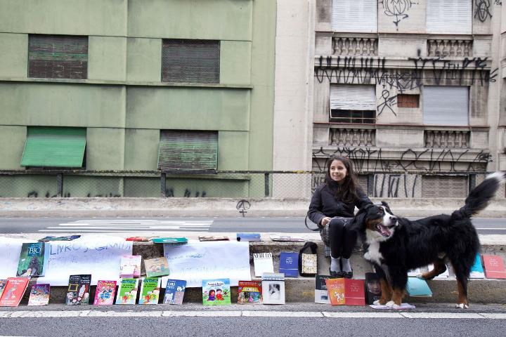Menina doa livros no Minhocão